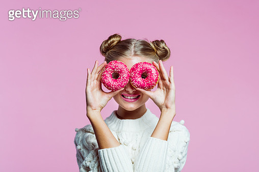 Portrait of happy teenager wearing white sweater. Girl holding pink donuts in front of her eyes, smiling at camera. Studio shot on pink background. - gettyimageskorea