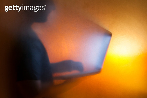 Man using laptop behind translucent glass with warm background - gettyimageskorea