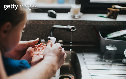 Adult helping kid to wash hands under a tap. - gettyimageskorea