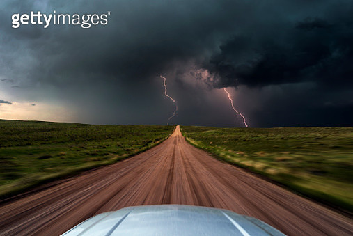 High speed storm chasing, taken from the roof of a moving car off road with double lightning bolts ahead. Colorado, USA. - gettyimageskorea