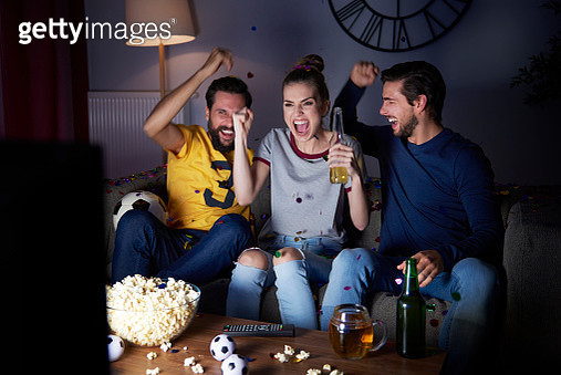 Excited friends sitting on the sofa watching Tv - gettyimageskorea