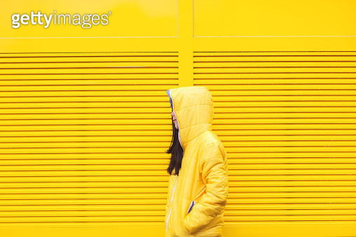 a brunette girl n yellow raincoat standing in front of a yellow wall - gettyimageskorea