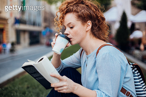 Young girl sipping coffee and reading a book - gettyimageskorea