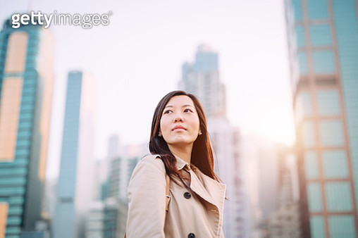 Confident young Asian woman looking up to sky with smile on a fresh bright morning against city skyline - gettyimageskorea