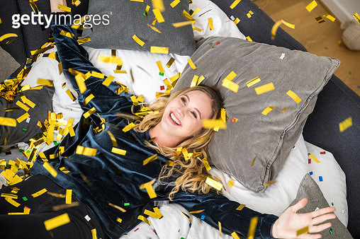Portrait of happy young woman with flying confetti at home - gettyimageskorea