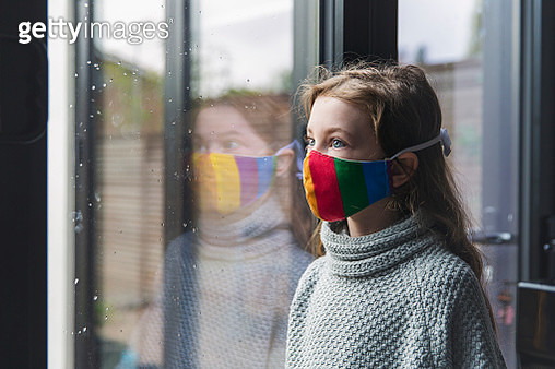 Young girl in rainbow mask by window - gettyimageskorea