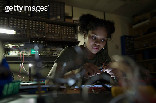 Focused female engineer working with electronics in dark workshop - gettyimageskorea