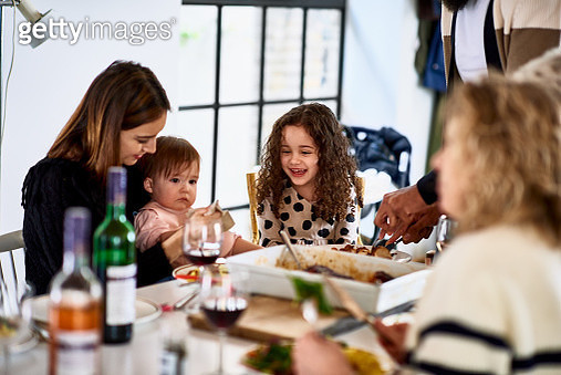 Mother with two children smiling at dinner table - gettyimageskorea