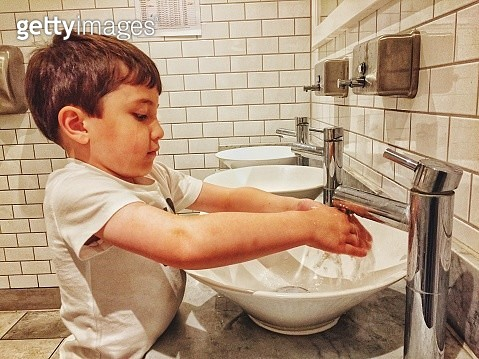 Side View Of Cute Boy Washing Hands In Sink At Public Restroom - gettyimageskorea