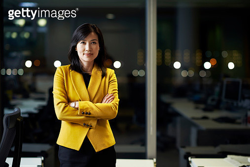 Woman standing in office at night - gettyimageskorea