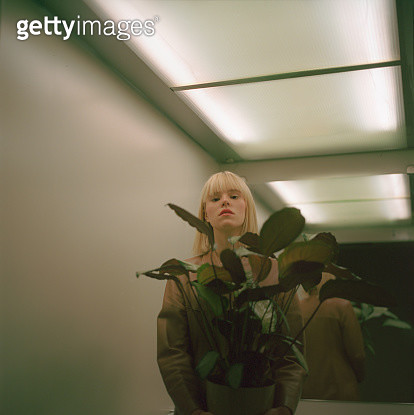 Portrait of beautiful young woman with long blond hair wearing brown coat standing inside elevator and holding a plant. - gettyimageskorea