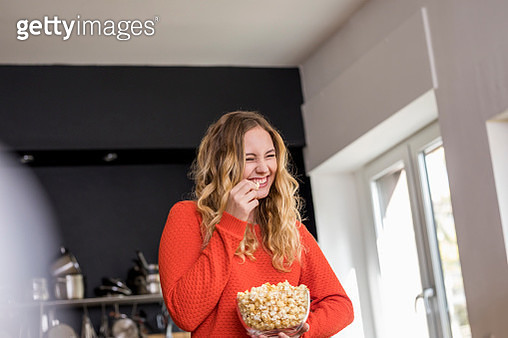 Portrait of giggling young woman with bowl of popcorn in the kitchen - gettyimageskorea