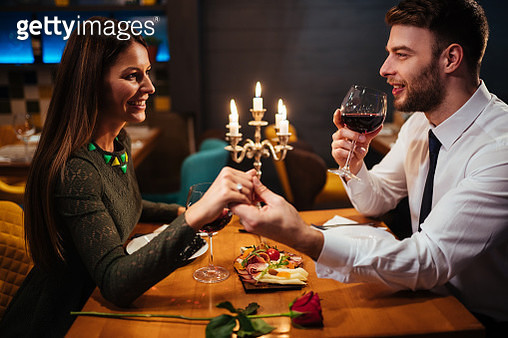 Couple holding hands during romantic dinner in a restaurant - gettyimageskorea