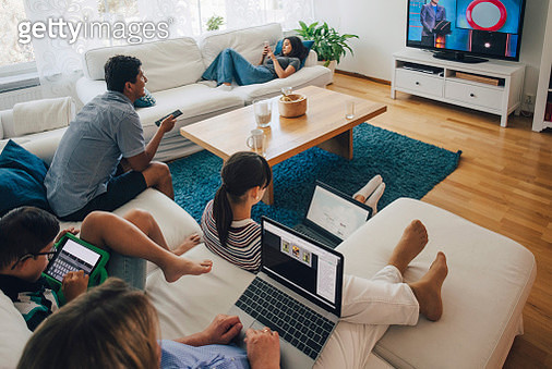 High angle view of family using technologies while relaxing in living room at home - gettyimageskorea