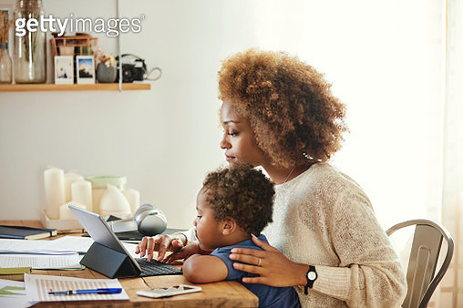 Mother with son working on digital tablet at home - gettyimageskorea