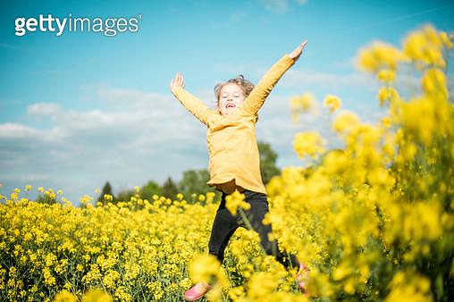 Carefree girl jumping in rape field - gettyimageskorea