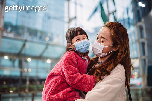 Mom & daughter in medical face masks talking joyfully in train station - gettyimageskorea