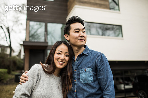 Portrait of young couple in front of new home - gettyimageskorea