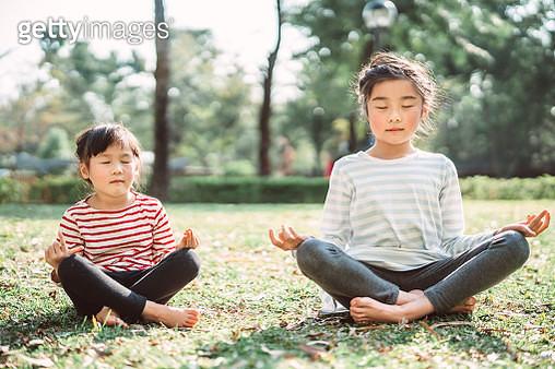 Sibling practicing yoga meditation on the lawn joyfully - gettyimageskorea