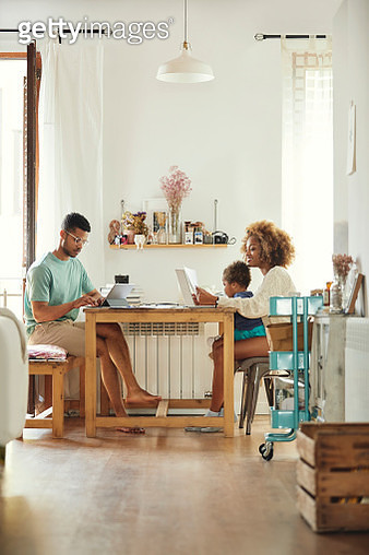 Parents working while sitting with son at home - gettyimageskorea