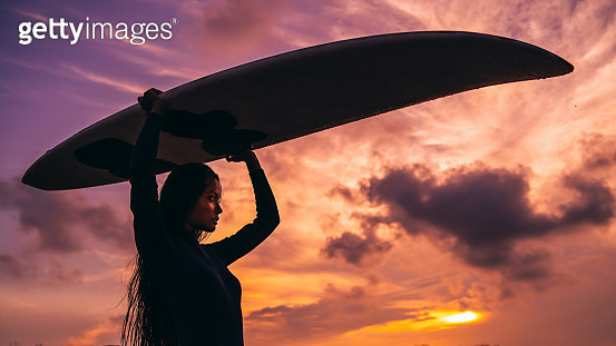 Asian woman carrying over her head surfboard on sunset - gettyimageskorea
