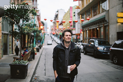 Young man standing on the sidewalk in San Francisco, Chinatown area, having a coffee break. - gettyimageskorea