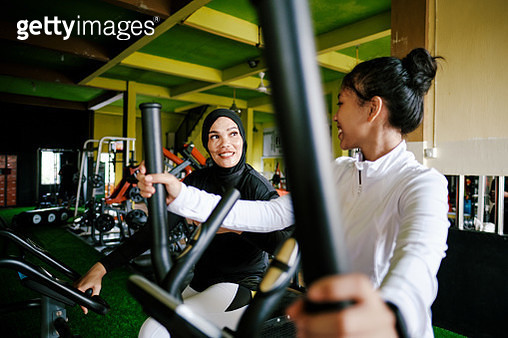 Mother and Daughter Exercising Using Exercise Bike at The Gym - gettyimageskorea