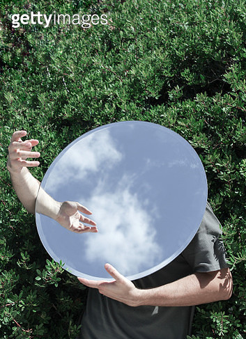 High Angle View Of Man Covering Face With Mirror While Standing On Field - gettyimageskorea