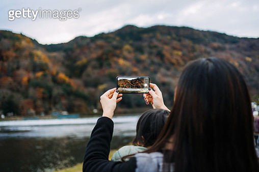 Young Asian mother carrying little daughter walking outdoors and photographing the beautiful Autumn nature scenics with smartphone while on vacation - gettyimageskorea