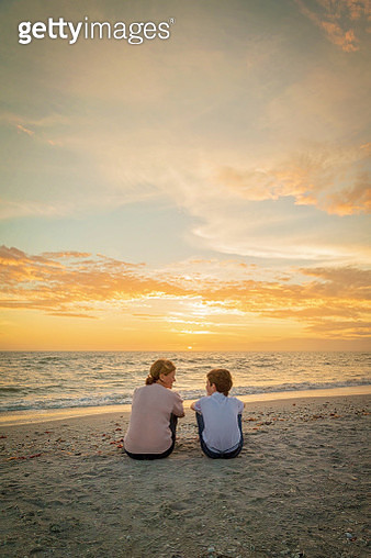 Mom and son age 12, sitting on sandy beach, talking and looking at each other with sea and sunset behind them. - gettyimageskorea