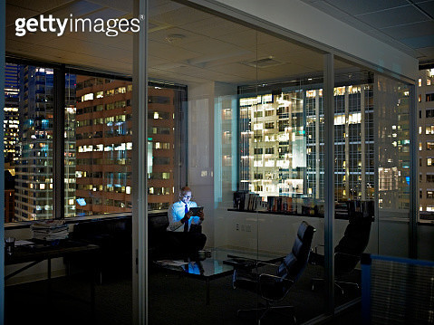 Businessman with digital tablet in office at night - gettyimageskorea