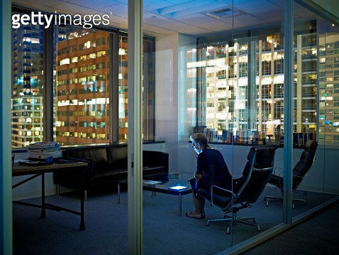 Woman with digital tablet in office at night - gettyimageskorea