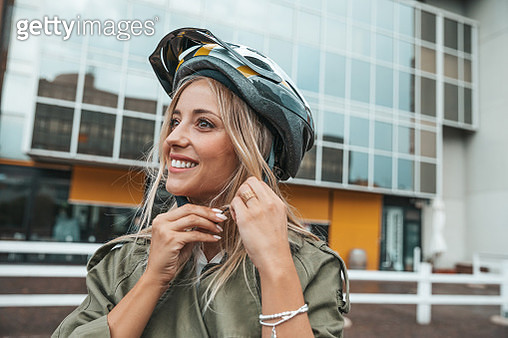 Woman putting helmet on and ready to ride - gettyimageskorea