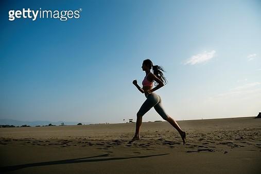 Woman jogging at beach. - gettyimageskorea