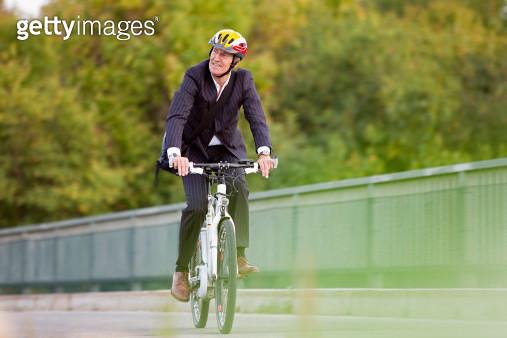 Businessman riding bicycle on bridge - gettyimageskorea