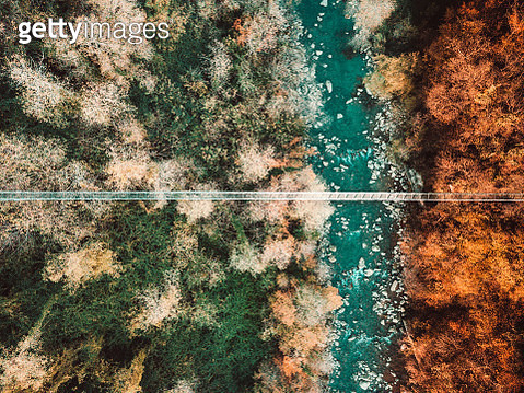 Aerial view of a suspension bridge over a creek and a forest - gettyimageskorea