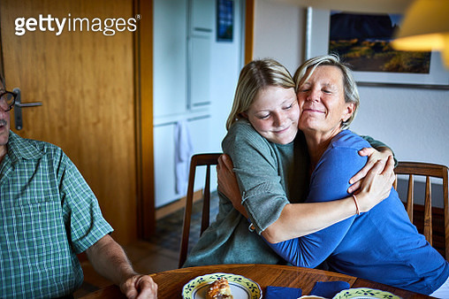 Adult granddaughter and grandmother hugging at dining table - gettyimageskorea