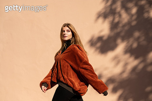 Woman walking past a wall with shadow of a tree - gettyimageskorea