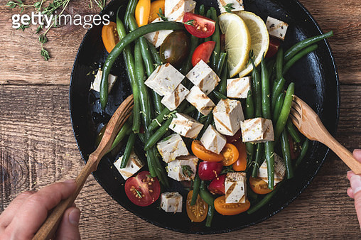 Delicious summer vegan meal, cooking healthy green beans salad with grilled tofu, fresh colorful mix cherry tomatoes, thyme herbs and lemon zest served in rural cast iron skillet, wooden forks, top view - gettyimageskorea