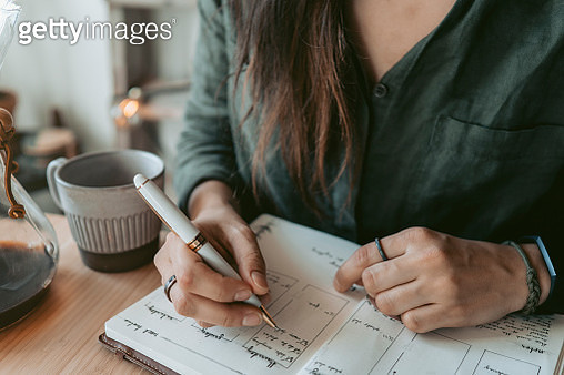 Woman taking notes in her diary - gettyimageskorea