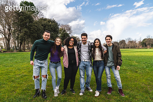 Group of six friends at the park together, embracing and looking at camera - Teamwork concept. Multi ethnic group of teenagers friends together. - gettyimageskorea