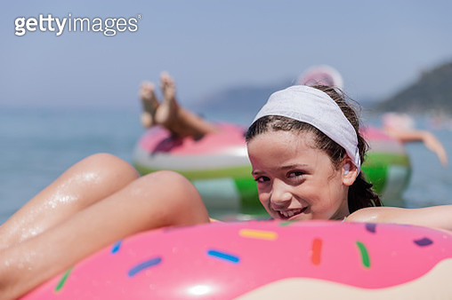 Smiling young child having fun when floating on swimming ring - gettyimageskorea