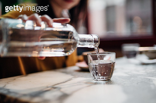 Close up shot of woman pouring water into glass at restaurant - gettyimageskorea