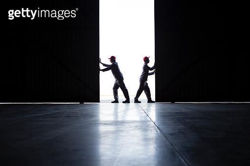 Two men pushing open doors - gettyimageskorea