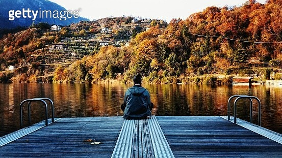Rear View Of Man Sitting On Jetty Over Lake Against Trees - gettyimageskorea