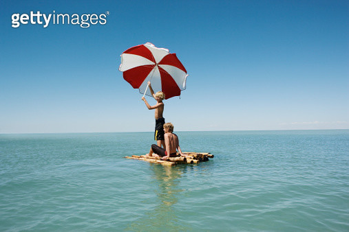 Two boys (10-12) on bamboo raft in sea, one holding up parasol - gettyimageskorea