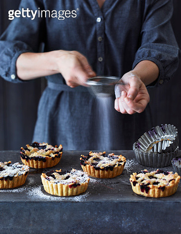 Woman Sifting Powdered Sugar Over Blueberry Tarts - gettyimageskorea