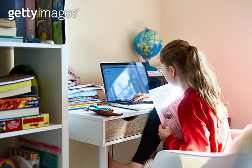 Young girl using laptop in bedroom during lockdown - gettyimageskorea