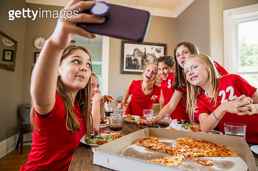 Girl taking selfie with friends while eating pizza - gettyimageskorea