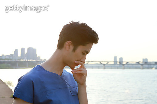 Thoughtful surgeon outdoors - gettyimageskorea